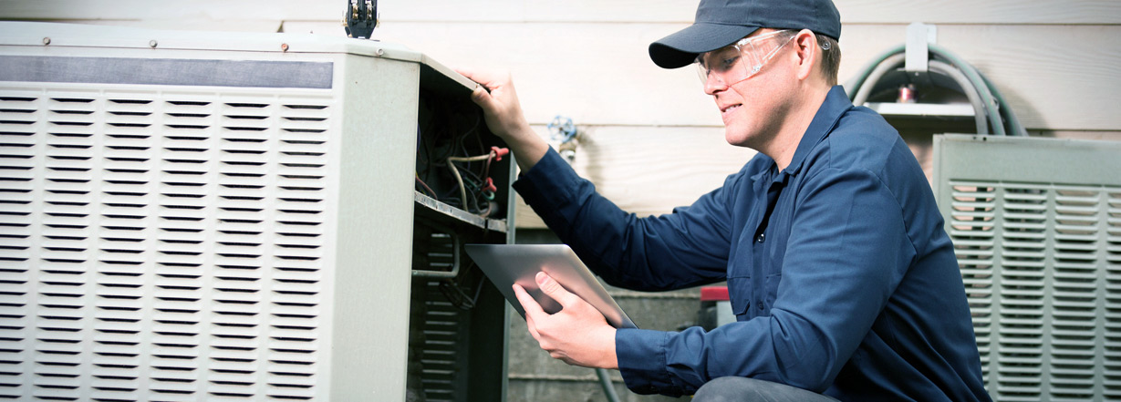 Image of technician working on industrial air conditioner outdoor unit.